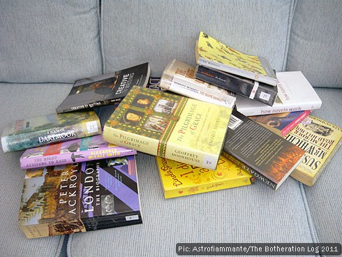 A heap of library books on a sofa