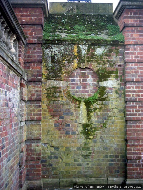 Decorative brickwork under a growth of lichen