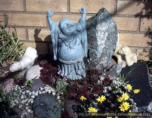 Laughing buddha statue in a sunny garden