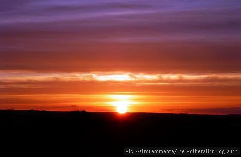 The sun sinking below the horizon