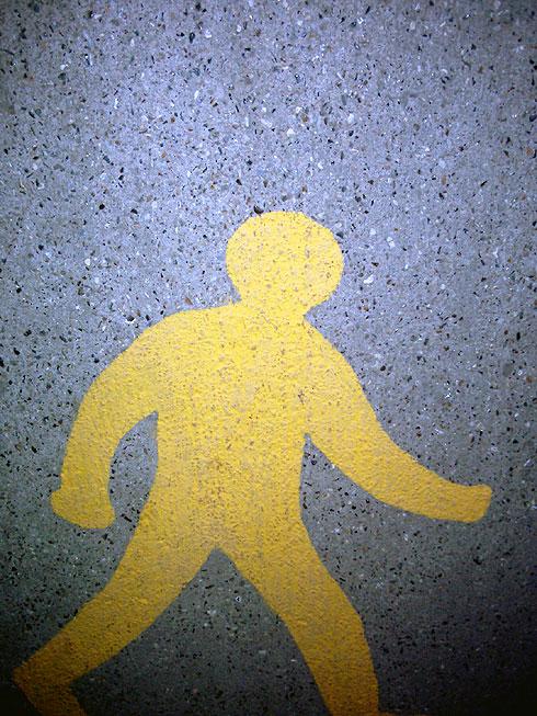 Yellow pedestrian symbol painted on tarmac