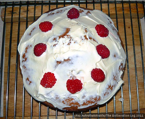 A sponge cake decorated with raspberries and cream