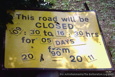 A sign announcing a road closure with jumbled letters and numbers