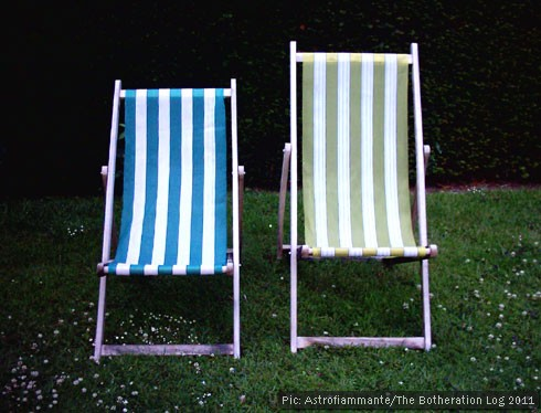 Two deckchairs side by side in a garden