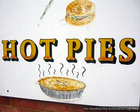 Painted sign outside shop advertising hot pies