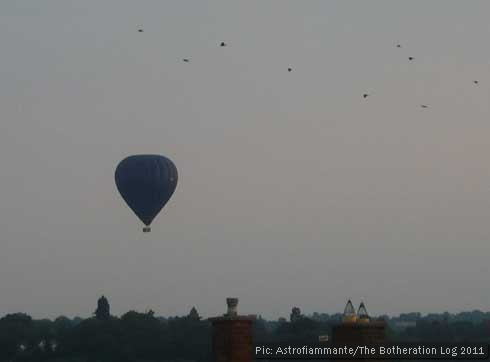 Hot air balloon floating over hills and rooftops with a flock of birds