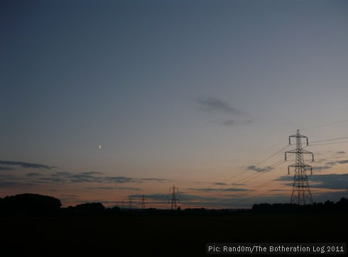 A line of transmission towers (pylons) sillhouetted against the evening sky