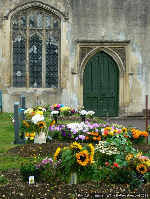 Church door and graves decorated with flowers