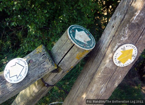 Waymarks on a series of fence posts pointing in different directions