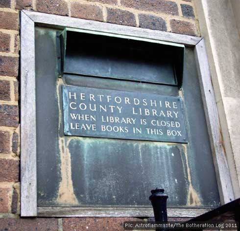 Former county library book-posting box set into brick wall