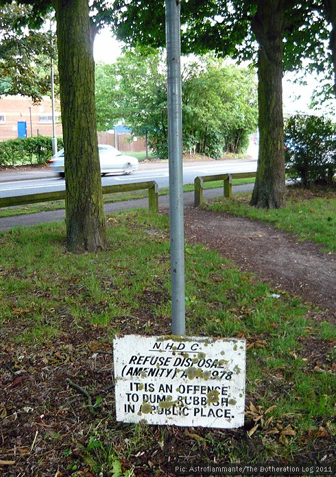 Old sign warning against dumping rubbish that has slid down its pole to ground level