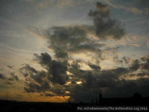 Dark grey clouds against a blue and orange sunset sky