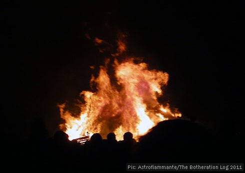 Visitors to a firework display sillhouetted against the bonfire