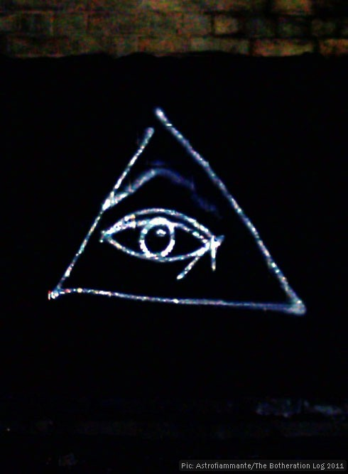 Graffito of an eye surrounded by a triangle in silver paint on a black viaduct wall.