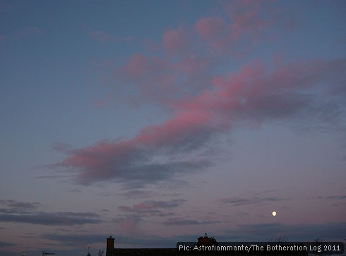 The moon heading down to the horizon below pink and blue clouds