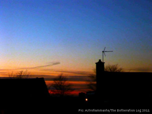 Strongly blue and orange sunset over dark roofline
