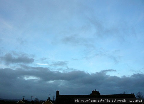Low grey cloud against a vivid blue sky