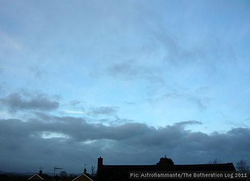 Low grey cloud against a vivid blue sky