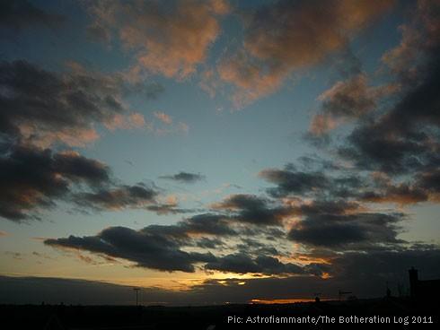 Bronze and dark-grey clouds against light-blue sky
