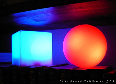 Two novelty coloured lights, one red and one turquoise-blue, on a bookshelf