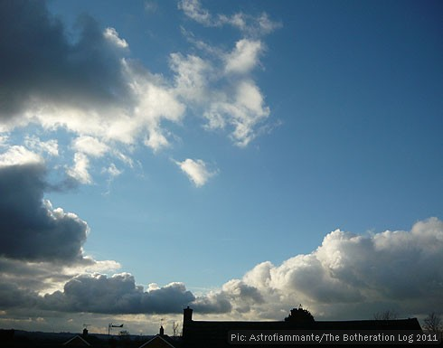 Rolling cumulus clouds against a blue sky, over rooftops