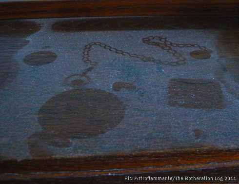 Outline of a pocket watch on an undusted surface