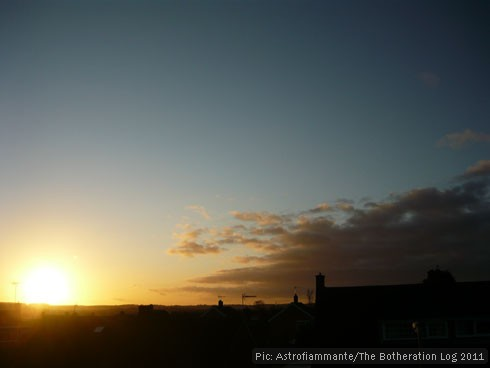 Sun about to set below horizon, against dark-blue sky and grey cloud