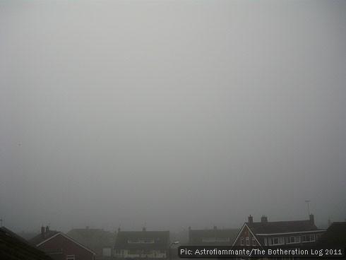 Foggy grey sky above rooftops