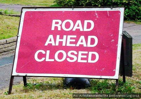 Red sign warning of road closures ahead