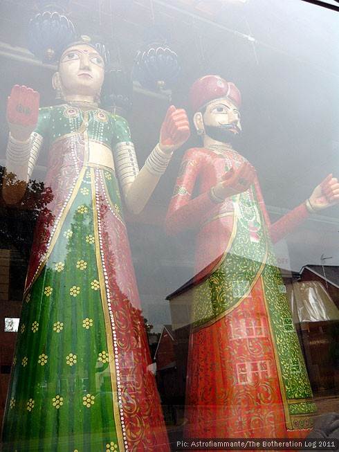 Life-size wooden figures in a shop window