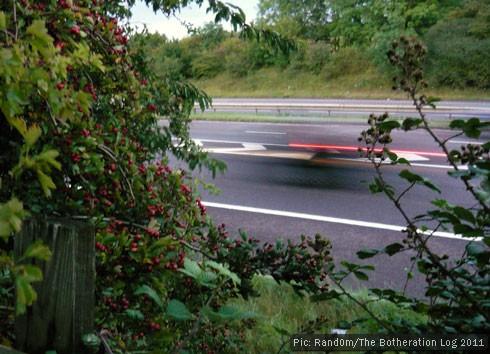 Long-exposure shot of a car racing past on a motorway