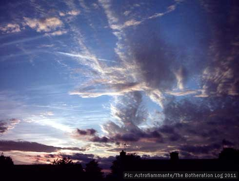 Sunset sky with roofline and contrails