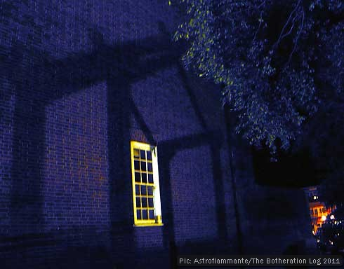 Shadow of house-like structure projected onto a brick wall with window