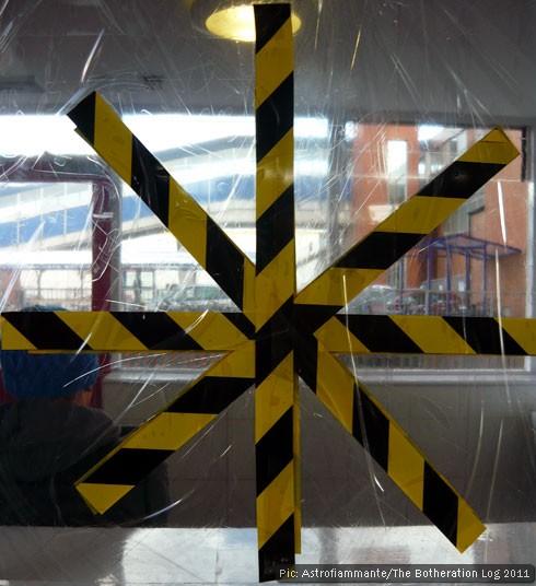 Black and yellow tape on a damaged window pane