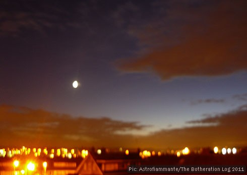 Long-exposure photograph of early evening sky, moon and clouds reflecting back streetlighting