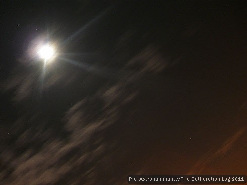 Long-exposure night photograph showing moon, clouds and streetlight glow
