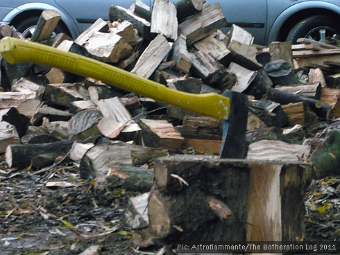 Yellow-handled axe stuck in stump surrounded by chopped firewood