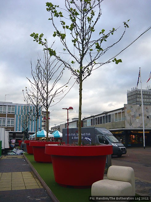 Tree saplings planted in giant red flowerpots in a town centre
