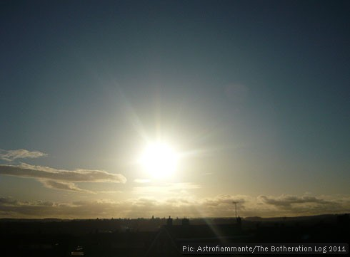 Blue sky with clouds on horizon and bright sun in the centre of the image