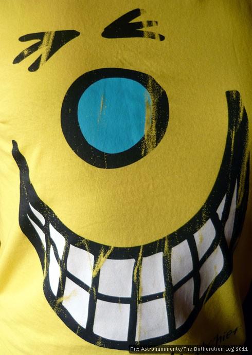 Yellow T-shirt depicting smiling cartoon face