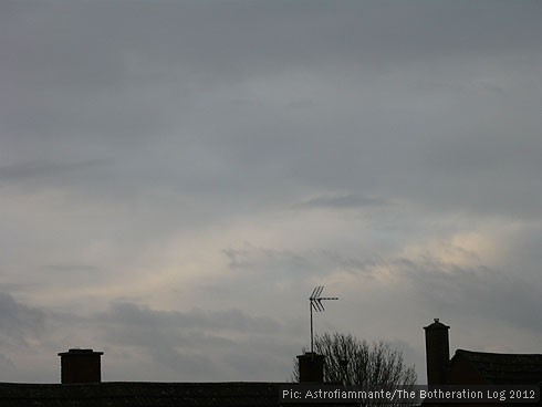 Sillhouetted trees and chimneys against a dark, cloudy sky